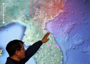 A quake official at the Korea Meteorological Agency (KMA) in Seoul points to North Korea's northeastern county of Kilju, where the communist country apparently conducted a nuclear test on 12 February 2013.