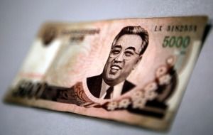 North Korean leader Kim Il-sung is seen on this 5000 North Korea won banknote in this photo illustration taken in Shanghai May 23, 2013. Chinese currency and U.S. dollars are being used more widely than ever in North Korea instead of the country's own money. The use of dollars and Chinese yuan, or renminbi, has accelerated since a revaluation of the North Korean won in 2009 wiped out the savings of millions of people, said experts on the country, defectors and Chinese border traders. The black market exchange rate for this 5000 North Korean won banknote is equivalent to $0.65, while the official North Korean exchange rate stands at more than $65. To match Insight KOREA-NORTH/MONEY REUTERS/Carlos Barria (CHINA - Tags: POLITICS BUSINESS) - RTX109LL